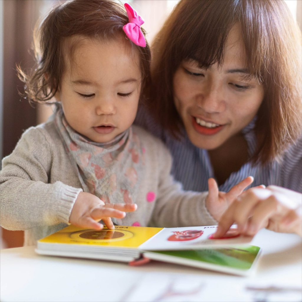 A parent and young child reading a story together.