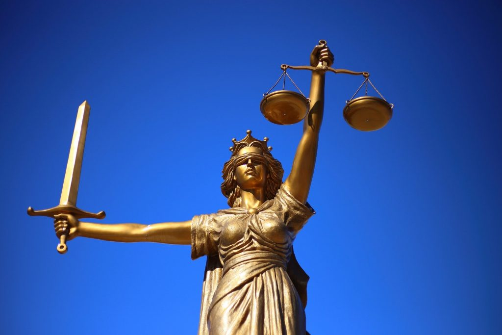 Statue of a woman in blindfold holding a sword and the figurative scales of justice.
