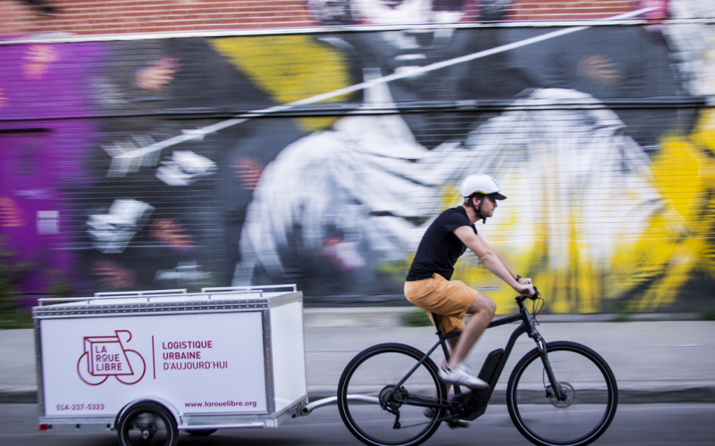 Man on a bicycle making a delivery to customers at home.