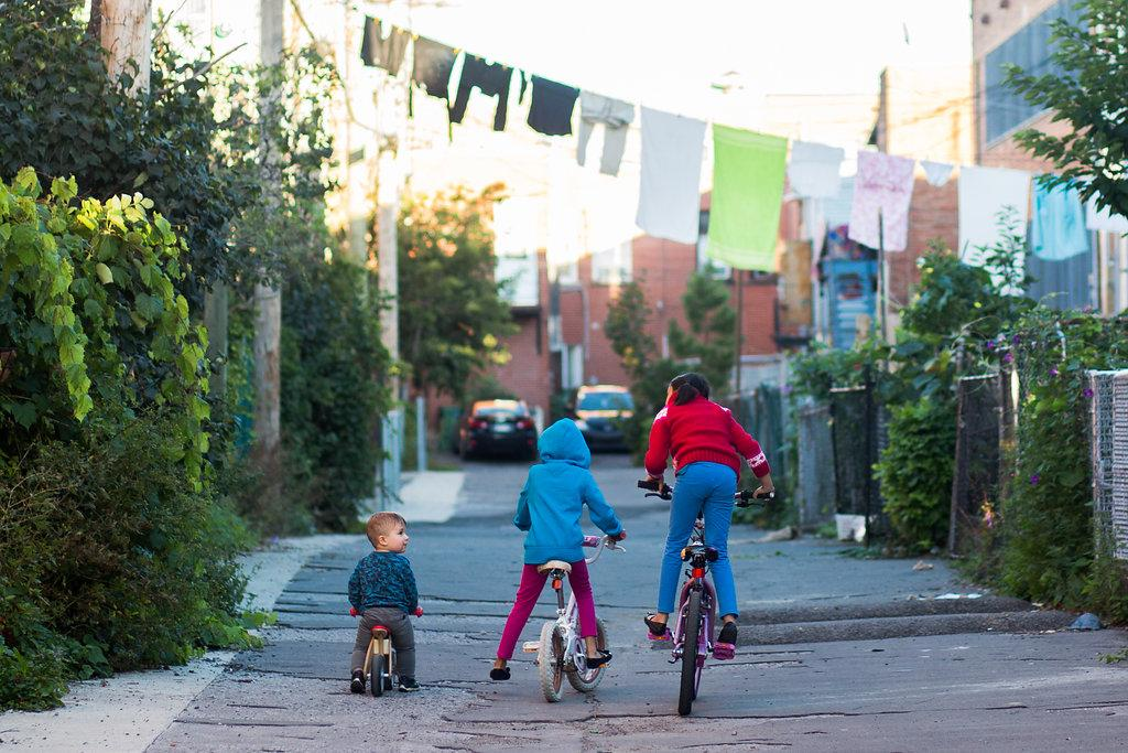 Children on bicycles in a street in Montreal's Park Extension borough.